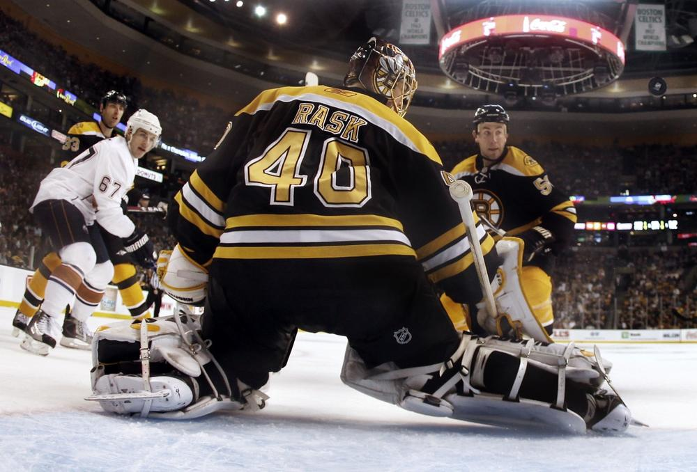 Bruins goalie Tuukka Rask (40) makes a save as Oilers center Gilbert Brule (67) looks for the rebound with  Boston defenseman Derek Morris, right, in Boston, Saturday. (AP/Winslow Townson)