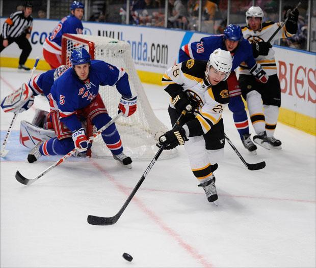 New York Rangers' Dan Girardi (5) defends the goal as  Boston Bruins' Mark Recchi (28) skates after the puck in the first period of the game on Sunday.  (Stephen Chernin/AP)