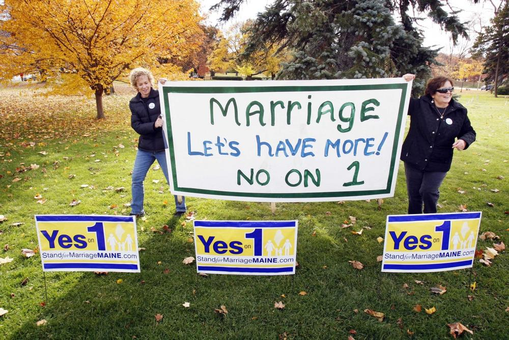 "Supporters of same-sex marriage Suzanne Blackburn, left, and Ann DiMella, of Portland, Maine, prepare to set up a ""No on 1"" sign on Tuesday (Robert F. Bukaty/AP)"