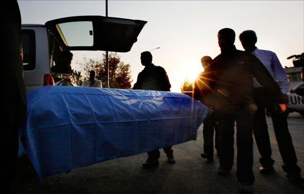 U.N. staff unload a coffin during a ceremony on Tuesday to transfer the remains of their two fellows who were killed when gunmen attacked a guest house. (Gemunu Amarasinghe/AP)