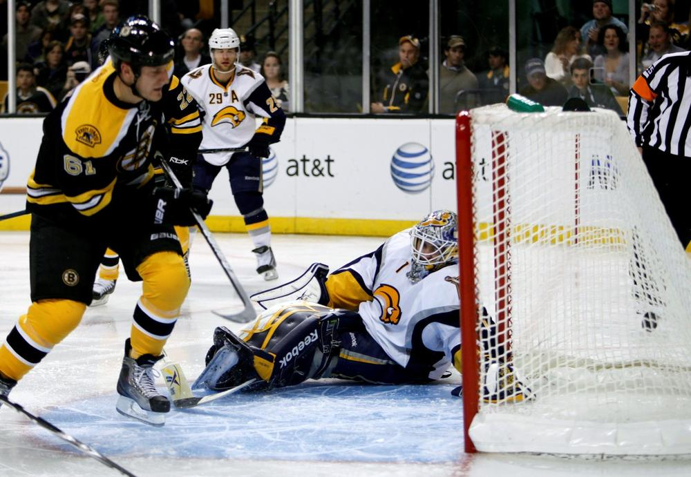 Bruins' Byron Bitz, left, scores on Sabres' Jhonas Enroth in the second period in Boston. (AP Photo/Michael Dwyer)