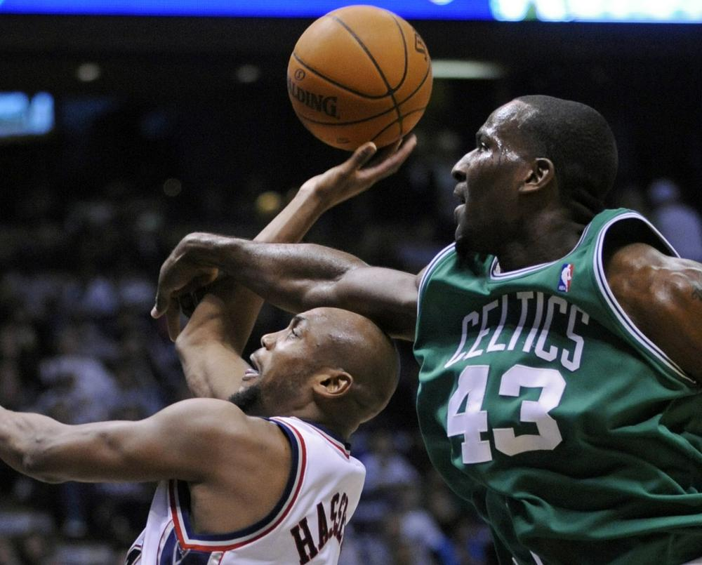 New Jersey Nets' Trenton Hassell, left, is fouled by Boston Celtics' Kendrick Perkins during the second quarter. (AP Photo/Bill Kostroun)