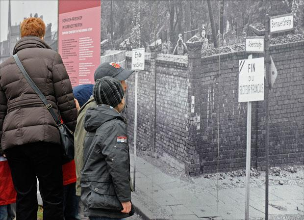 "Children look at historical photo exhibits during a commemoration ceremony for the 20th anniversary of the fall of the Berlin Wall at the memorial ""Bernauer Strasse"" in Germany. (Fabian Bimmer/AP)"