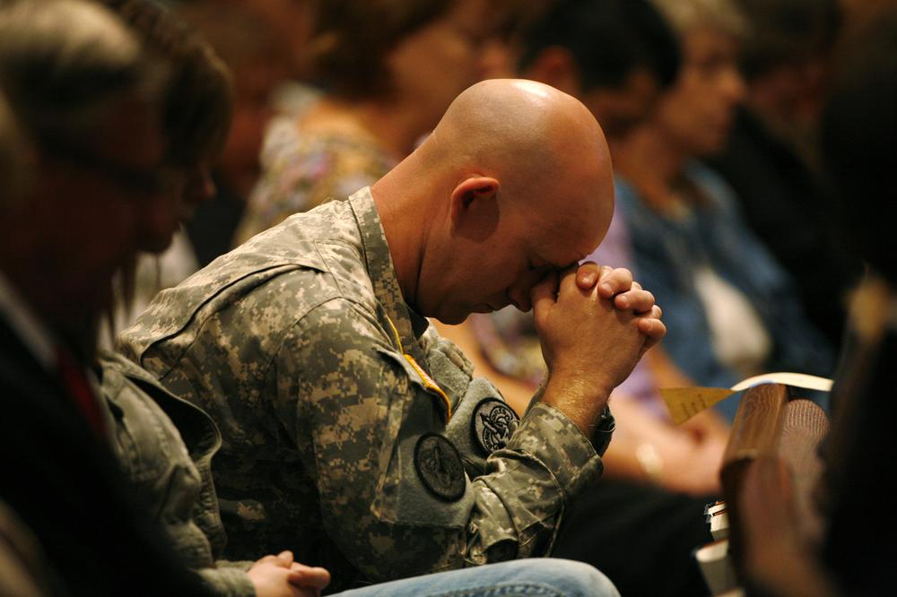 U.S. Army Sgt. Andrew Sobecky bows his head during a prayer service at First Baptist Church, Sunday, Nov. 8, 2009, in Killeen, Texas.   (AP)