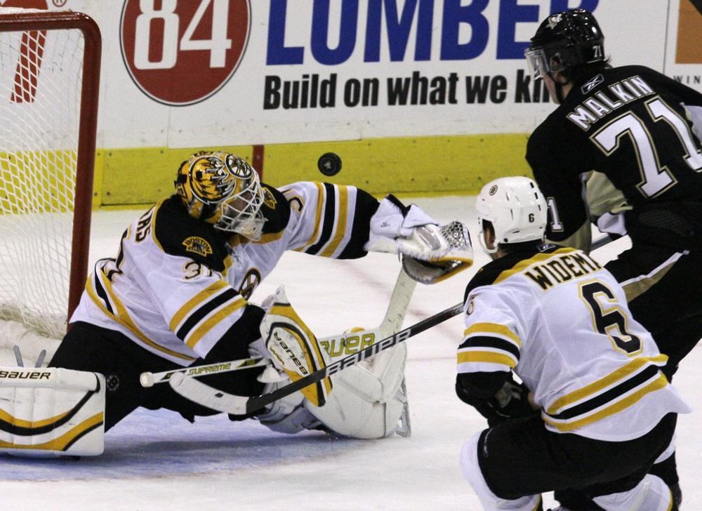 Bruins goalie Tim Thomas, left, makes a second-period save on a shot by Penguins' Evgeni Malkin (71) with Bruins' Dennis Wideman trailing the play in Pittsburgh, Saturday. (AP Photo/Gene J. Puskar)