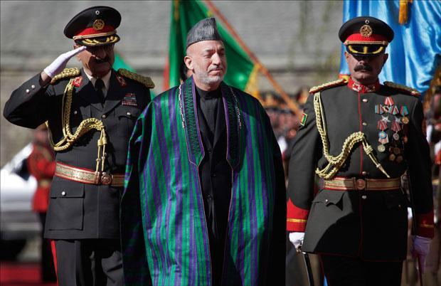 Afghanistan's President Hamid Karzai greets the guards of honor as he arrives to the Presidential Palace for his inauguration in Kabul. (Anja Niedringhaus/AP)