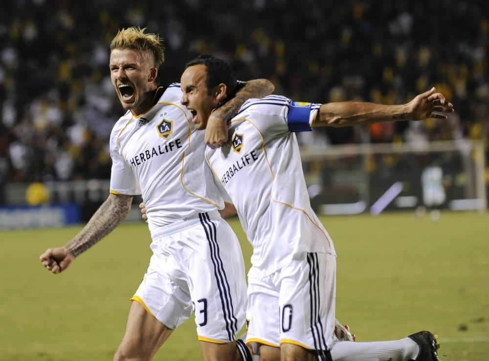 Los Angeles Galaxy's David Beckham, left, celebrates teammate Landon Donovan's penalty goal kick during their MLS Western Conference Championship match, Nov. 13. The presence of the two star players in the MLS championship game is a boon to the league, says WBUR's sports commentator. (AP)