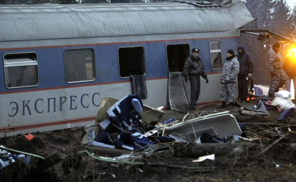 Russian police officers inspect a damaged coach at the site of a train derailment near the town of Uglovka, some 400 km (250 miles) north-east of Moscow, Russia on Saturday.  (AP Photo/Ivan Sekretarev)