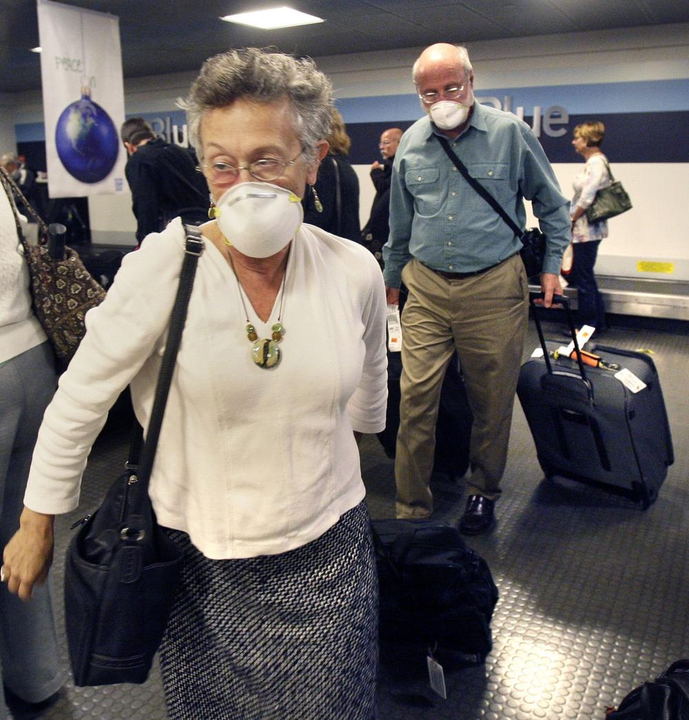 A couple wearing masks for protection from swine flu arrives at Logan International Airport in Boston on Tuesday after flying in from Puerto Rico. (AP)