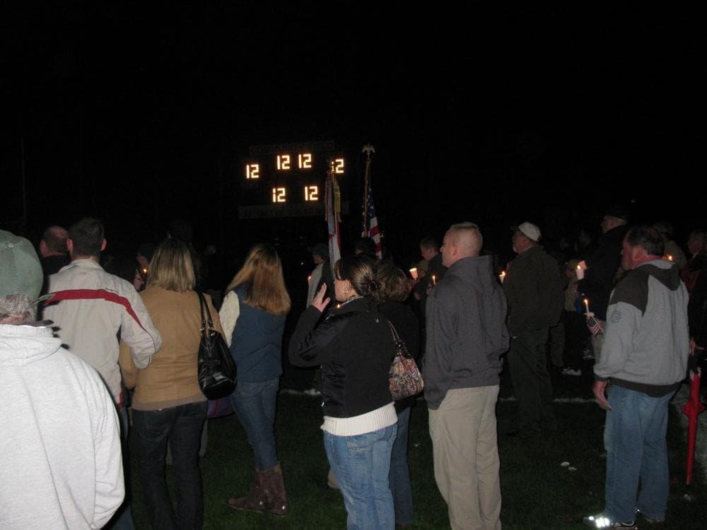 Kyle VanDeGiesen's Number 12 lights the scoreboard during a candlelight vigil in North Attleborough
