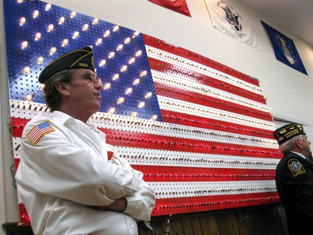 Marine Corps Sgt. Mark Sherman watches Wednesday as Gov. Deval Patrick signs new veterans' benefits into law. (Meghna Chakrabarti/WBUR)
