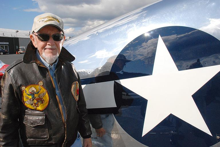 George Sutcliffe with a restored P-51 Mustang fighter plane in Norwood. (Sarah Bush/WBUR)