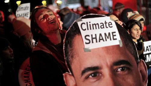 Demonstrators hold a picture of U.S. President Barack Obama during a demonstration outside the Bella Center, the venue of the U.N. Climate Conference in Copenhagen, Denmark, early Saturday, Dec. 19, 2009. (AP)
