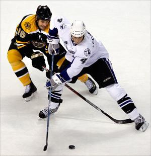 Bruins left wing Marco Sturm and Lightning center Vincent Lecavalier vie for the puck on Wednesday. (Elise Amendola/AP)