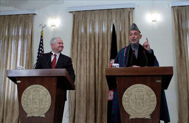Defense Secretary Robert Gates looks on as Afghan President Hamid Karzai speaks during a joint press conference at the presidential palace in Kabul. (Musadeq Sadeq/AP)