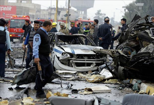 Iraqi security forces gather at the site of a bomb attack near the Labor Ministry building in Baghdad. (Hadi Mizban/AP)
