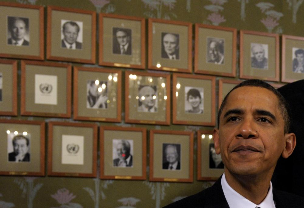 President Barack Obama sits in front of framed photos of previous Nobel Peace Prize winners during a Signing Ceremony at the Norwegian Nobel Institute in Oslo, Norway, Thursday, Dec. 10, 2009. (AP)