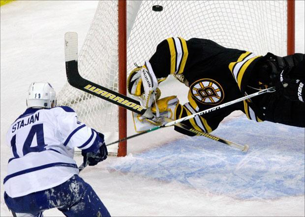 Goalie Tuukka Rask dives to try to make a save on a shot by Toronto Maple Leafs' Matt Stajan during the third period on Thursday. (Charles Krupa/AP)