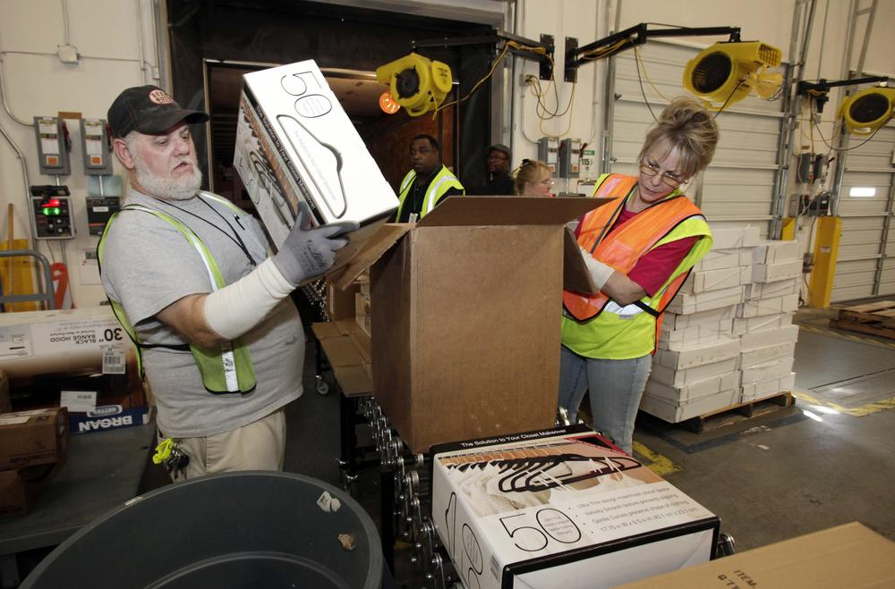 Workers unpack a truck inside the 800,000 sq. ft. Amazon.com warehouse in Goodyear, Ariz, Nov. 16, 2009,. (AP)