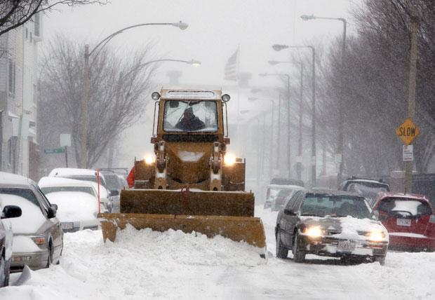 A snow plow clears a street in Boston on Sunday. (Michael Dwyer/AP)