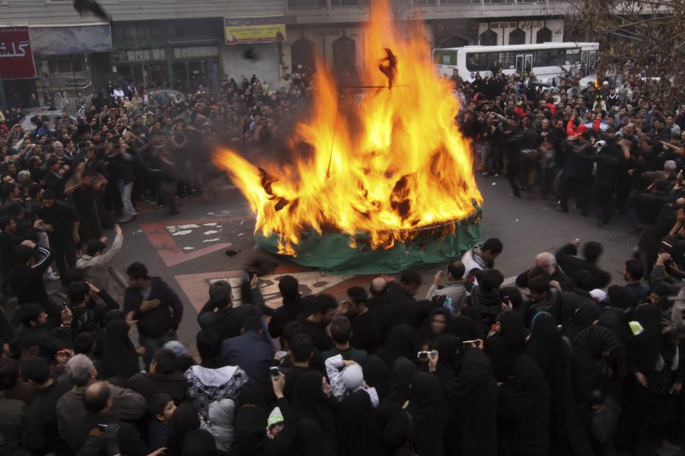 Iranian mourners attend a ceremony commemorating Shiites' holy day of Ashoura, in Tehran, Iran, Sunday, Dec. 27, 2009, marking the death of Imam Hussein, a grandson of Islam's prophet Mohammed, who was killed in a 680 A.D.in a battle at Karbala in Iraq.  Mourners burned a green tent, as a symbol of Imam Hussein's tent. (AP)