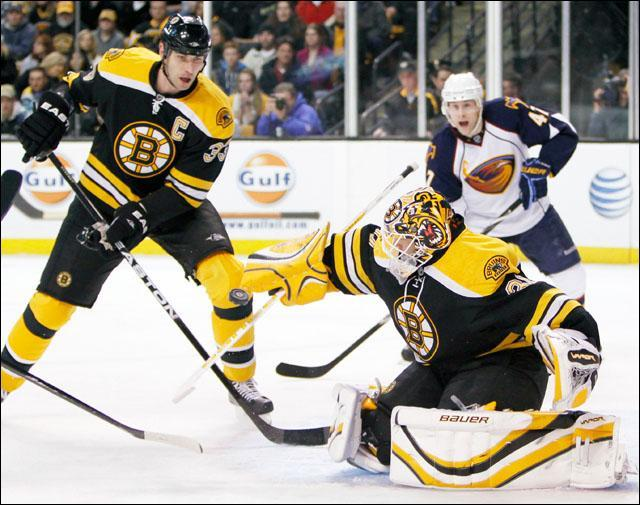 Boston Bruins' Tim Thomas, center, blocks a shot as Zdeno Chara, left, of Slovakia, and Atlanta Thrashers' Rich Peverley, right, look on in the first period of a game on Wednesday. (AP)