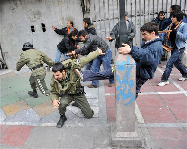 Iranian protesters beat police officers during anti-government protest in Tehran on Sunday. (AP Photo)