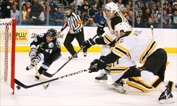 Tampa Bay Lightning left winger Martin St. Louis puts the puck past Boston Bruins defensmen Zedeno Chara (33) and Dennis Wideman (6) on Monday. (Chris O'Meara/AP)