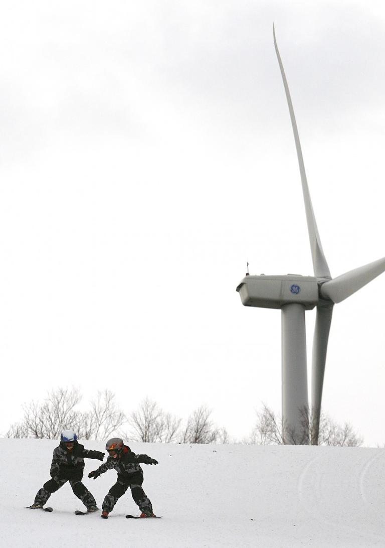 Ryan Dood, 8, left, reaches to help stabilize his younger brother, Evan, 7, as they ski down a Jiminy Peak Mountain Resort slope in front of the facility's 1.5-megawatt wind turbine in 2008. (AP)