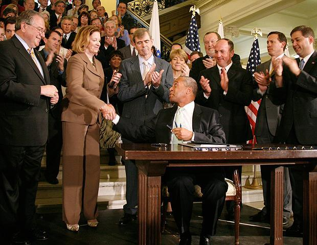 Massachusetts Gov. Deval Patrick, seated right, shakes Senate President Therese Murray's hand after signing an ethics bill on July 1, 2009, in Boston. Among state officials watching are Speaker of the House Robert DeLeo, left, and Secretary of State William Galvin, third from right. (AP)