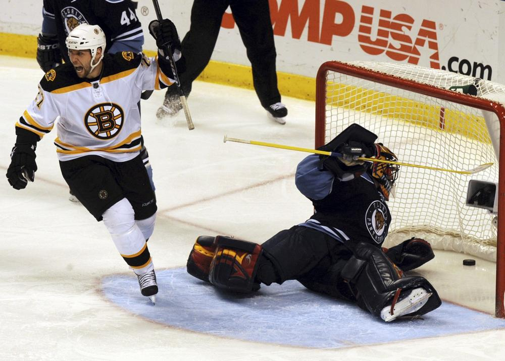 Boston Bruins' Steve Begin, left, celebrates as Florida Panthers goalie Scott Clemmensen drags the puck out of the net after Bruins' Marco Sturm scored in the third period of an NHL hockey game Sunday, Dec. 27, in Sunrise, Fla. (AP)