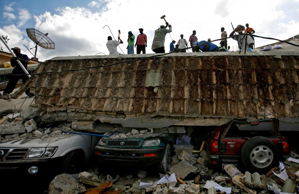 People search for survivors under the rubble of a collapsed building the day after an earthquake hit Port-au-Prince, Haiti, Wednesday, Jan. 13, 2010.  (AP)