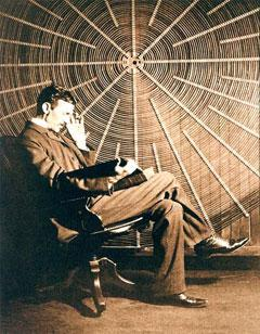 In this undated photograph, Nikola Tesla sits in front of the spiral coil of his high-voltage transformer at East Houston St., New York. (Wikimedia Commons)