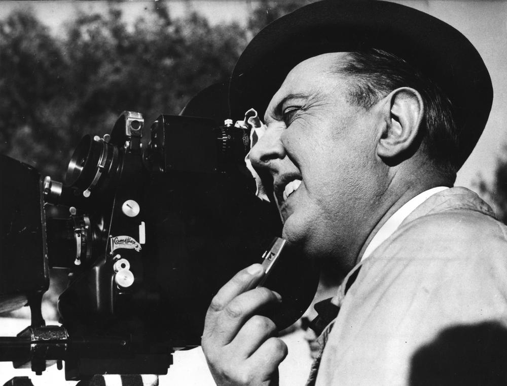 """French movie producer, Jacques Tati shoots a scene,  jumping in the role as camera man on the set producing his latest and third film """"Mon Uncle"""" (My Uncle) in France, April 1958. (AP)"""