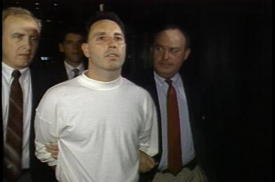 """Vincent """"The Animal"""" Ferrara is arrested in 1989 on racketeering and related charges. At right is Boston Police Det. Martin Coleman, now retired, who worked alongside Assistant U.S. Attorney Jeffrey Auerhahn on the Organized Crime Strike Force in the 1980s. (David Boeri)"""