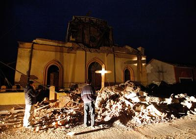 People stand next to the destroyed cathedral of Chanco, some 180 miles southwest of Santiago on Sunday. (AP)