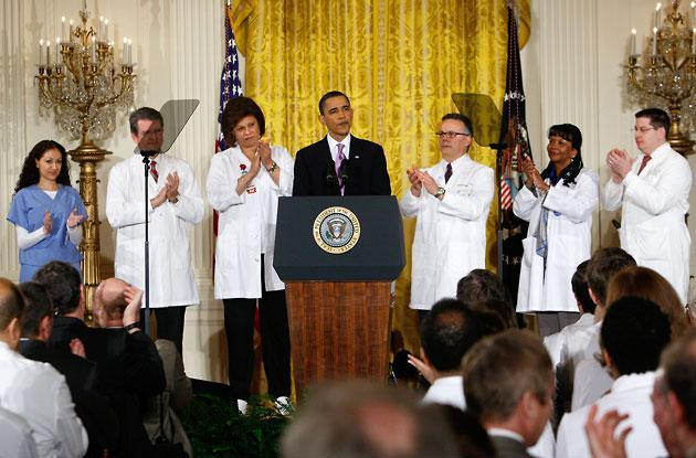 President Obama stands with health care professionals as he speaks about health care reform Wednesday in the East Room of the White House. (Charles Dharapak/AP)