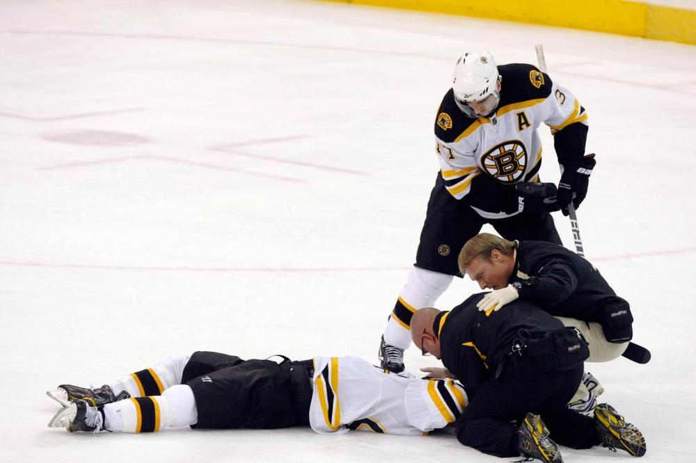 Boston Bruins' Patrice Bergeron, top, watches as trainers look over teammate Marc Savard after he was hit in the third period of an NHL hockey game against the Pittsburgh Penguins in Pittsburgh, Sunday, March 7, 2010. The Penguins won 2-1. (AP)