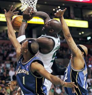 Boston Celtics' Kevin Garnett, center, has a shot blocked by Washington Wizards' Nick Young, left, and James Singleton in the second quarter of Sunday's game. (AP Photo/Michael Dwyer)