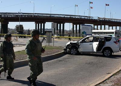 Soldiers stand at a crime scene where the crashed car of a U.S. Consulate employee sits in Ciudad Juarez, Mexico on Sunday. The employee and her husband were shot to death Saturday in the car, with their baby unharmed in the backseat, near the Santa Fe International Bridge linking Ciudad Juarez with El Paso, Texas. (AP)