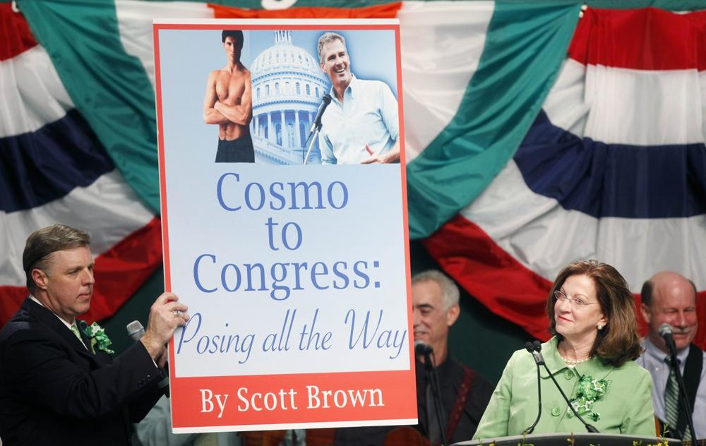 State Sen. Jack Hart holds up a mock book cover brought to the stage by Massachusetts Senate President Therese Murray, right. (AP)