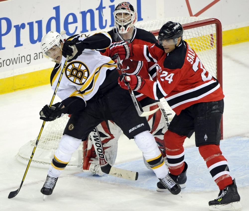 New Jersey Devils' Bryce Salvador, right, checks Boston Bruins' Blake Wheeler, left, in front of Devils goaltender Martin Brodeur during the third period of an NHL hockey game Monday, March 15, 2010, in Newark, N.J. The Devils beat the Bruins 3-2. (AP Photo)