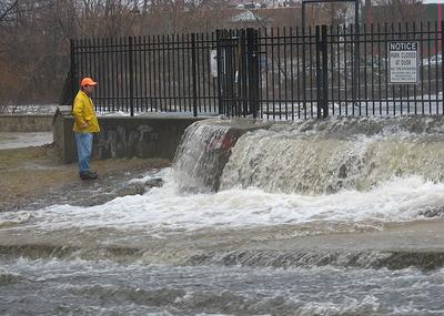 An official surveys flooding of the Charles River by the Moody Street dam in Waltham on Monday.  (Jack Lepiarz for WBUR)