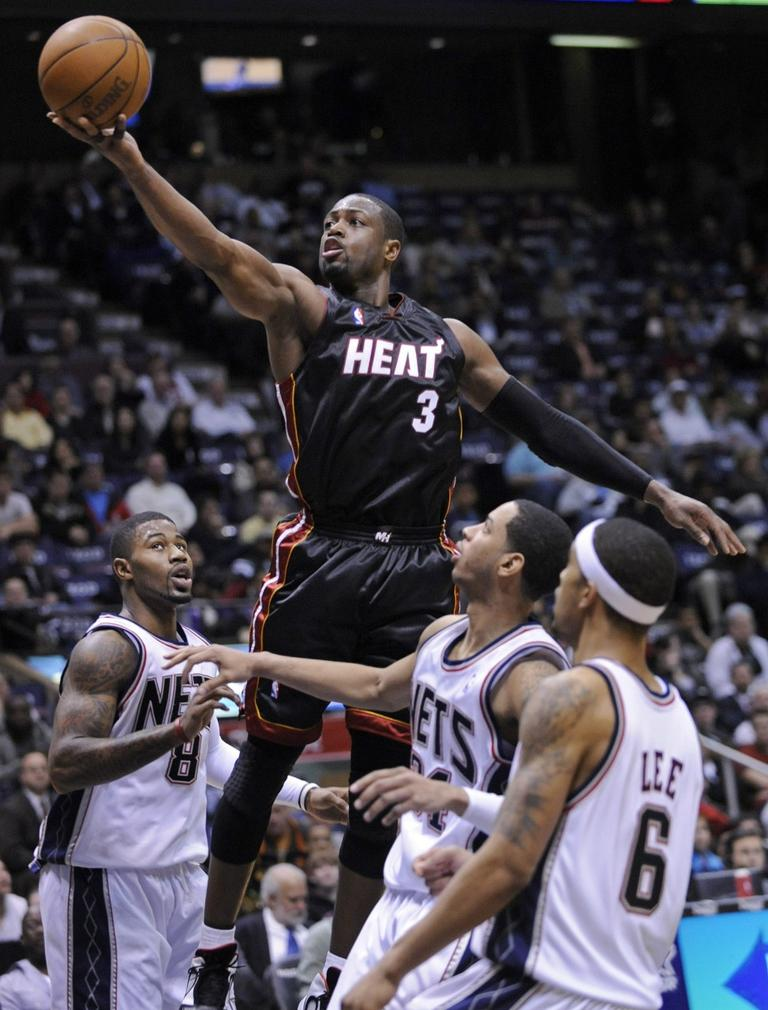 Rising easily over the Nets, the Miami Heat's Dwyane Wade puts up a shot. (AP)