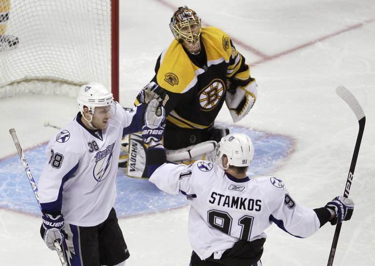 Boston Bruins goalie Tuukka Rask, center, of Finland, watches as Tampa Bay Lightning center Paul Szczechura, left, is congratulated by Steven Stamkos, right, after his third-period goal during Thursday's game. (AP Photo)