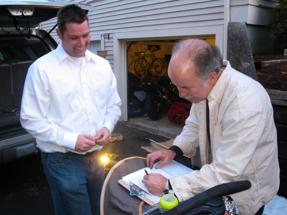 Joe Truschelli gets a signature from Chris Benning to get on the ballot in Plymouth. (Fred Thys/WBUR)