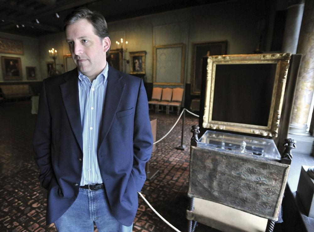 Anthony Amore stands beside empty frames from which the thieves took two of the paintings. (AP)