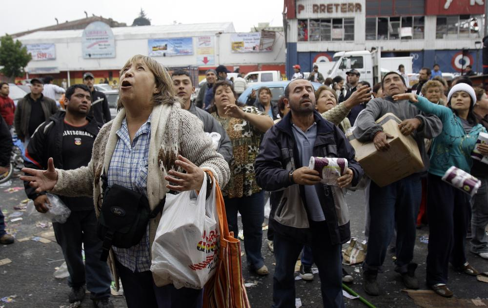 People wait to catch goods thrown from a supermarket window during sporadic looting in Concepcion, Chile following Saturday's earthquake (AP)