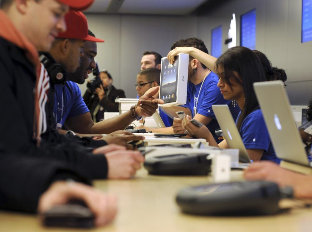 People purchase the iPad at the Apple store on Fifth Ave. in New York, Saturday. Eager customers have been lining up outside Apple Stores and some Best Buys to be among the first to buy one as sales started at 9 a.m. Saturday in each time zone. (AP Photo/Diane Bondareff)