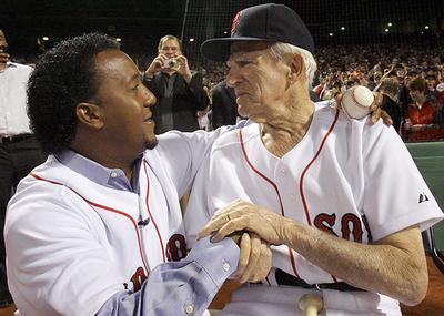 Former Boston Red Sox pitcher Pedro Martinez hugs former Red Sox player Johnny Pesky after Martinez threw out the ceremonial first pitch before the opener. (AP)